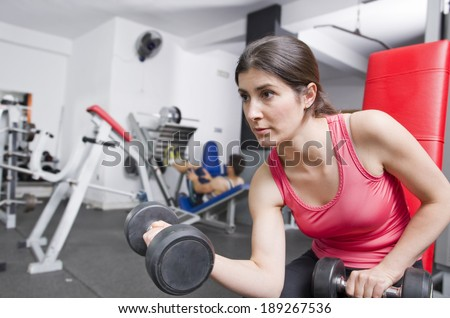 Woman posing in gym room ready for fitness biceps exercises - stock photo