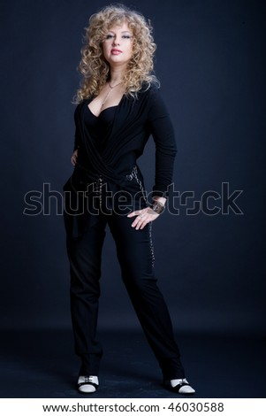 Woman posing on a dark background - stock photo