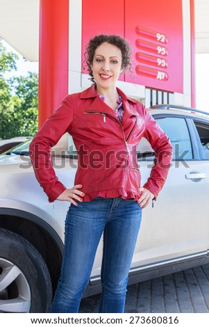 woman posing on background of a car on gasoline station - stock photo