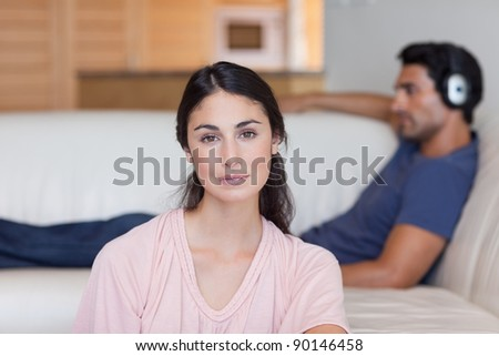 Woman posing while her boyfriend is listening to music in their living room