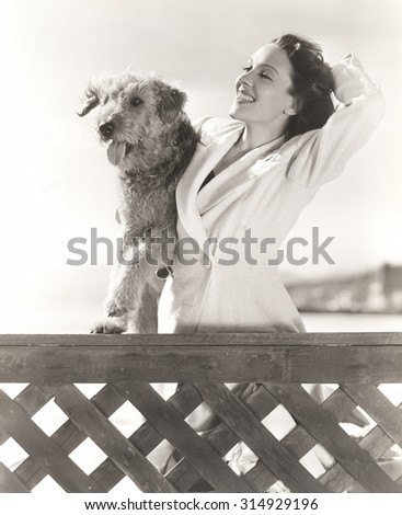 Woman posing with her Airedale at the beach - stock photo