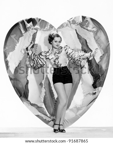 Woman posing with large heart - stock photo
