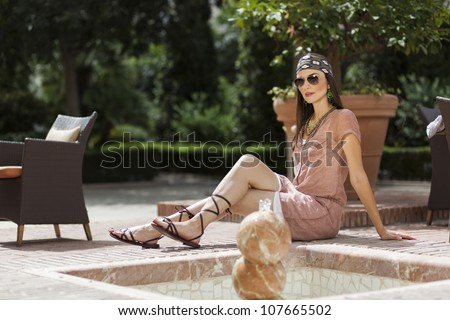 Woman posing with sunglasses and bandanna in a fountain - stock photo