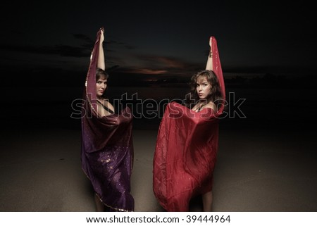 Woman posing with veils in the dark - stock photo