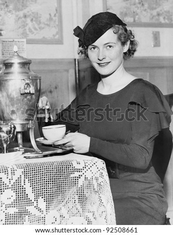 Woman pouring coffee from a coffee urn - stock photo
