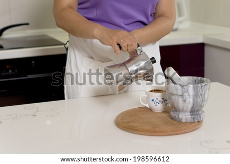 Woman pouring coffee from a percolator into a cup on a kitchen counter with a pestle and mortar alongside for grinding the coffee beans - stock photo