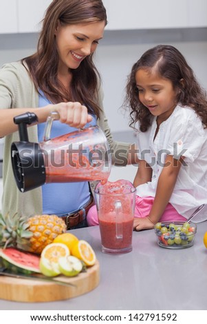 Woman pouring fruit from a blender into cup - stock photo
