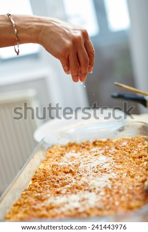 Woman pouring grated parmesan cheese on lasagna recipe in a tray - stock photo