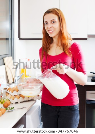 Woman pouring milk in bowl in home kitchen