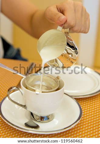 Woman pouring milk into cup filled with tea.