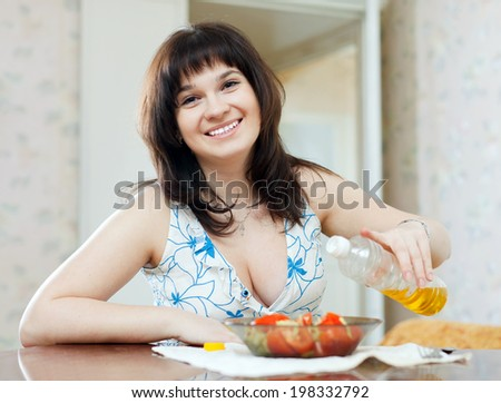 Woman pouring oil to vegetables salad