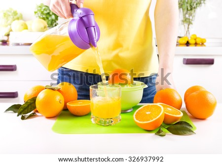 woman pouring orange juice into glass in a kitchen