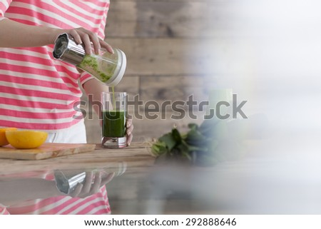 Woman pouring self made vegetable juice into a glass - stock photo