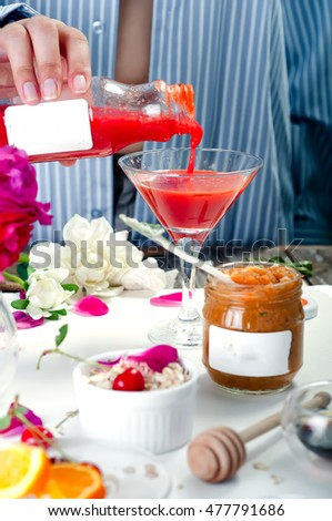 woman pours a glass of strawberry smoothie