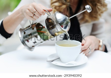 woman pours green tea from teapot into a cup - stock photo