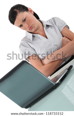 Woman pouting in front of her computer - stock photo