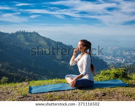 Woman practices pranayama yoga breath control in lotus pose padmasana outdoors in Himalayas in the morning on sunrise. Himachal Pradesh, India - stock photo