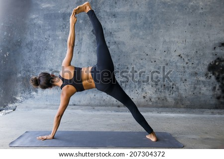 Woman practicing advanced yoga against a dark texturized wall - stock photo