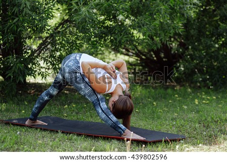 Woman practicing advanced yoga at the outdoor. A series of yoga poses - stock photo