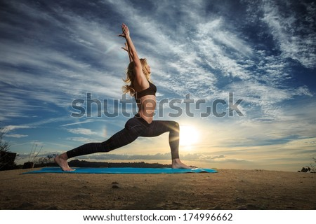 Woman practicing Warrior yoga pose outdoors over sunset sky background.  - stock photo