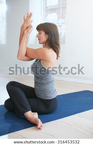 Woman practicing yoga, Garudasana, Eagle pose. Mature woman sitting on mat doing yoga with her arms and legs crossed. - stock photo