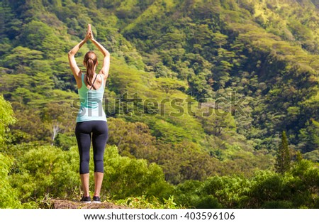 Woman practicing yoga in a green peaceful setting.  - stock photo