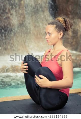 Woman practicing yoga near waterfall. Fetus Pose. Garbhasana - stock photo