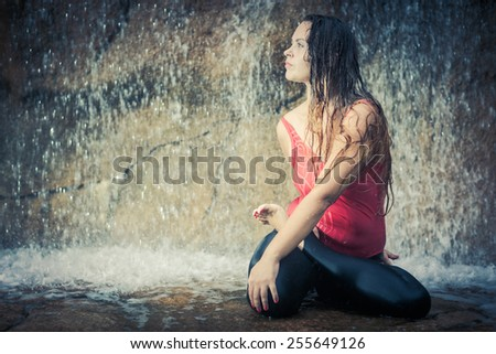 Woman practicing yoga near waterfall. Twisted lotusl Pose. Bharadvajasana - stock photo