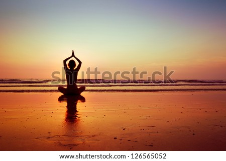Woman practicing yoga on the beach - stock photo