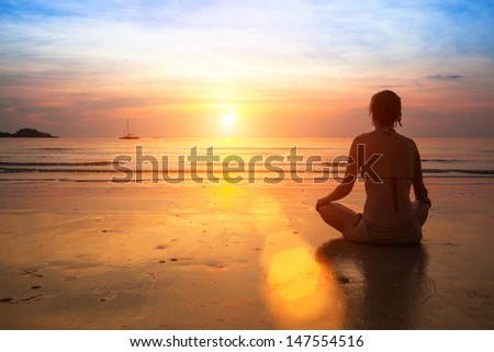 Woman practicing yoga on the ocean beach at sunset.