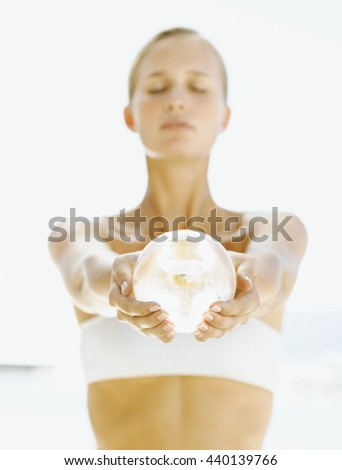 Woman practicing yoga with energy ball in her hands - stock photo