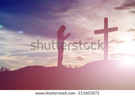 woman pray with cross silhouette, god concept - stock photo