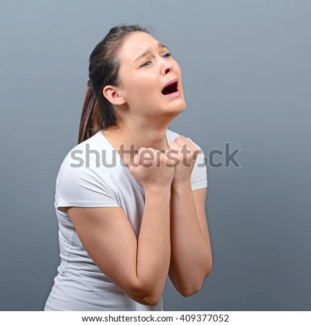 Woman praying about something or begging for mercy against gray background - stock photo