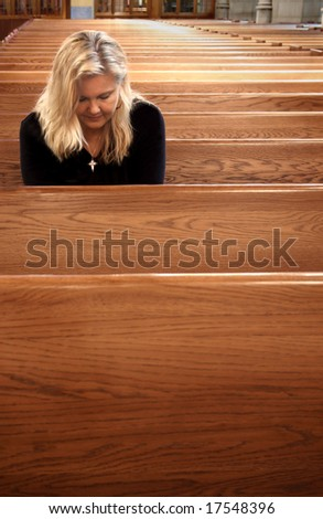 Woman praying in church - stock photo