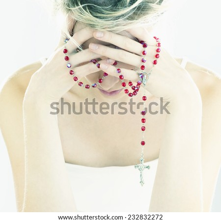 Woman Praying on Red Rosary - stock photo