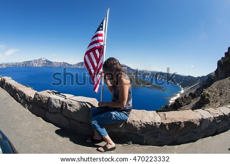 woman praying while holding American flag at Crater Lake, Oregon
