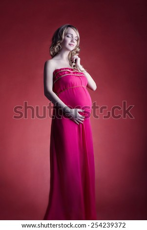 woman pregnant on red background - stock photo