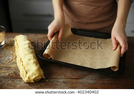 Woman preparing a baking tray for baking apple roll - stock photo
