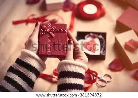 Woman preparing gift for wrapping for Valentine's Day - stock photo