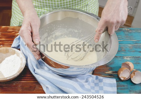 Woman preparing pancake batter.  Woman mixing eggs and wheat flour in a bowl - stock photo