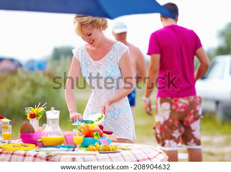 woman preparing picnic table in summer park - stock photo