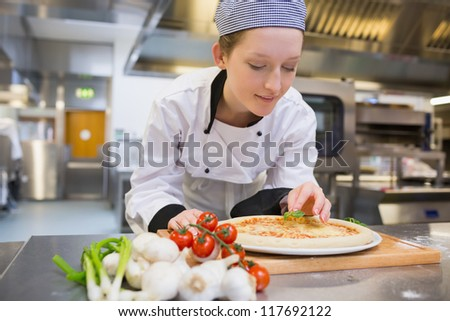 Woman preparing pizza in kitchen - stock photo