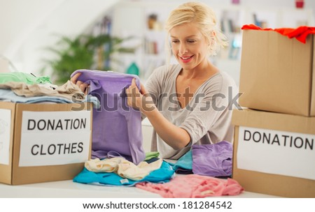 Woman preparing the old clothes she wants to donate for charity. - stock photo