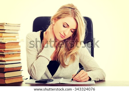 Woman preparing to exam, counting on calculator.