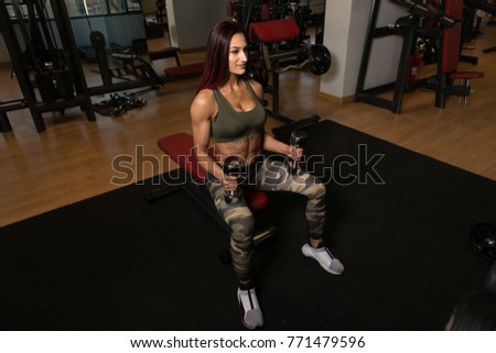 Woman Preparing To Exercising Shoulders With Dumbbells In The Gym And Flexing Muscles - Muscular Athletic Bodybuilder Fitness Model Doing Dumbbell Concentration Curls