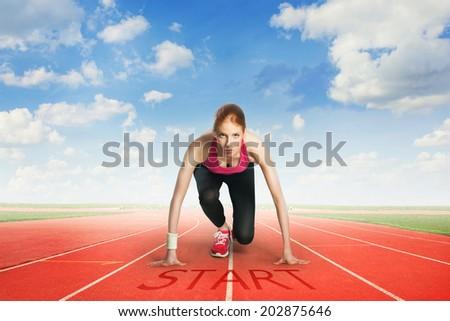 Woman preparing to run - stock photo