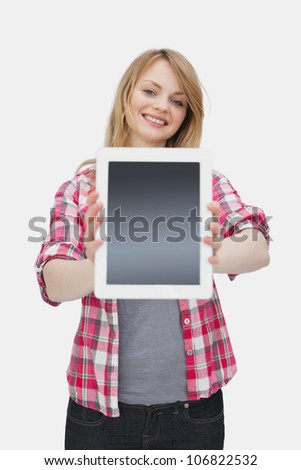 Woman presenting a tablet computer against a white background - stock photo