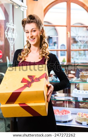 Woman presenting cake and pastries in takeaway boxes in cafe or pastry shop - stock photo