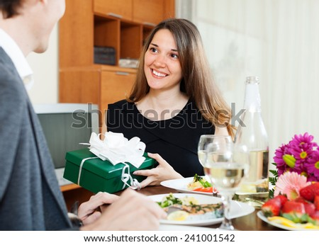Woman presenting gift to man at table during romantic dinner