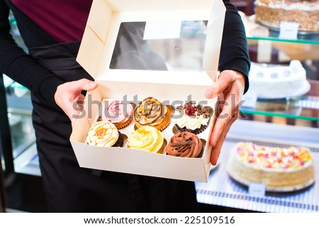 Woman presenting muffins and cupcakes in takeaway boxes in cafe or pastry shop - stock photo